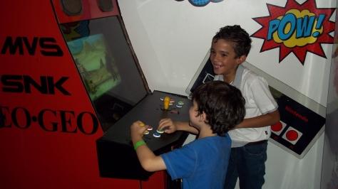 crianças jogando fliperama
